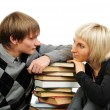 Young couple with stack of books isolated on white background — Stock Photo