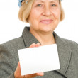 Senior woman with blue hard hat holding a blank card — Stock Photo #23810683