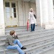 Man sitting on the steps and looks at a woman — Stock Photo #23810851