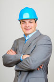 Happy businessman with blue hard hat standing confidently isolated on white background — Stock Photo