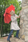 Fashion portrait of young attractive lady near stone wall — Stock Photo