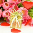 Stock Photo: Tulips with red heart and greeting card isolated on white background