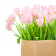 Tulips in paper bag against white background — Stock Photo #25008249