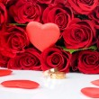 Red roses and two golden wedding rings — Stock Photo