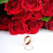 Red roses and two golden wedding rings — Stock Photo #25010641