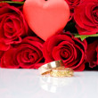 Red roses and two golden wedding rings — Стоковое фото #25011137