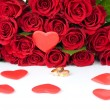 Red roses and two golden wedding rings - Stock Photo