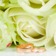 White roses and two golden wedding rings — Стоковое фото #25011551