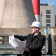 Engineer with white hard hat holding drawing - Stock Photo