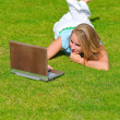 Young blonde woman lying on the grass field with laptop — Stock Photo