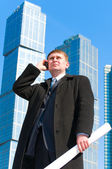 Businessman in front of skyscrapers — Stock Photo