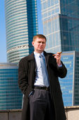 Businessman with cigar near skyscrapers — Stock Photo