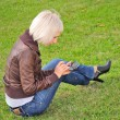 Woman with cellphone in park — Stockfoto