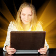 Woman holding magic laptop in her hands — Stock Photo #25550685
