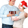 Young couple in santa's hats holding gift boxes isolated on white background — Stock Photo