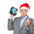 Businessman in santa's hat holding gift boxes isolated on white background — Stock Photo