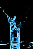 Salpicaduras de agua azul en el vidrio en fondo negro — Foto de Stock