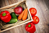 Fresh raw vegetables in the wooden box on the wooden table — Stock Photo