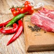 Fresh steaks with vegetables on the wooden table — ストック写真