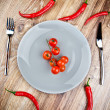 Red hot chili peppers and tomatoes on the plate on wooden table — Stock Photo