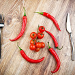 Red hot chili peppers and tomatoes on wooden table — Stock Photo