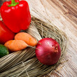 Fresh raw vegetables in the straw on the wooden table — Stock Photo