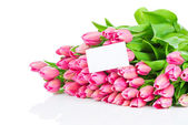 Bouquet of pink tulips and a greeting card — Stock Photo