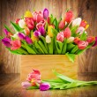 Tulips in the box on wooden background — Stock Photo #39367917