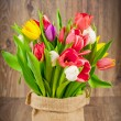 Stock Photo: Tulips in sack on wooden background