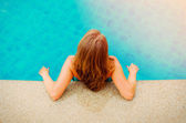 Young woman relaxing by the pool — Stock Photo