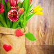Tulips in the sack on wooden background — Stock Photo