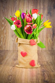 Tulips in the sack on wooden background — Стоковое фото