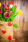 Tulips in the sack on wooden background — Foto Stock