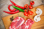 Fresh steaks with vegetables — Stock Photo