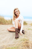 Blondie sitting on sand — Stock Photo