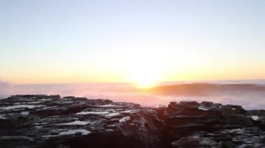 A beautiful sunrise in Australia with ocean waves crashing against rocks.