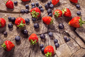 Blueberry and strawberries on wood in nature — Foto de Stock