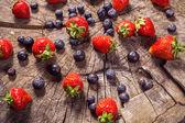Bosbessen en aardbeien op hout in de natuur — Stockfoto