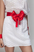 Red bow on a white dress on the grey background — Stock Photo