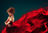 Femme en rouge soufflant volants robe rouge dissolvant en splash — Photo