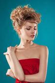 Bellissima modella bionda con i capelli ricci guardando giù, le mani piegate — Foto Stock