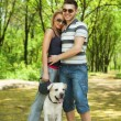 Young couple walking with dog in park — 图库照片