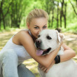 Attractive blond young girl playing with dog at the park — 图库照片