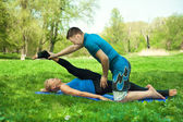 Woman does outdoor stretching with her personal trainer on a gre — Stock Photo