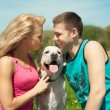 Young sports couple with a dog at the park — 图库照片