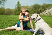 Una giovane coppia, seduto con un cane nel parco — Foto Stock