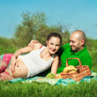 Young happy pregnant woman with young man lying on the grass hav — Stock Photo
