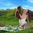 Beautiful pregnant woman relaxing in the park with a little dog - Stock Photo