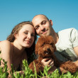 Portrait of happy couple with dog lying on the grass — Stock Photo #24872821