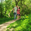 Pregnant couple walking at the park kissing and holding hands. F — Stock Photo
